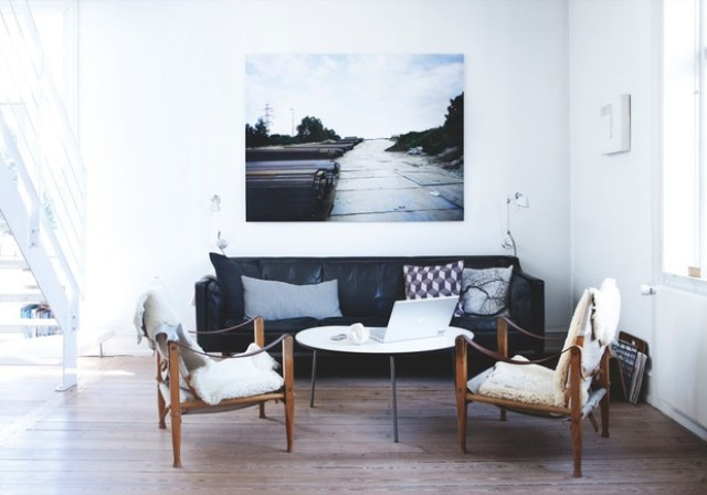 Bright living room in Copenhagen with a black sofa and leather chairs