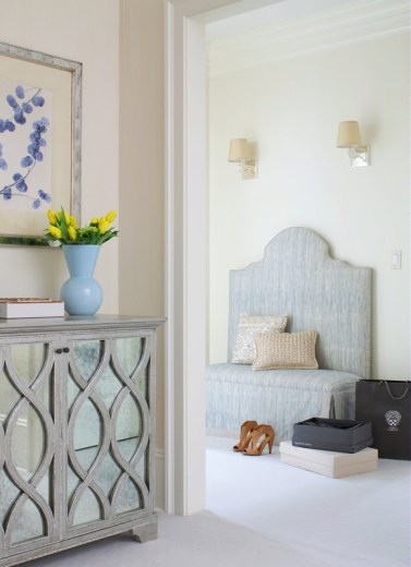 Dressing room with blue ottoman, accent pillows, two shoe boxes and a black shopping bag