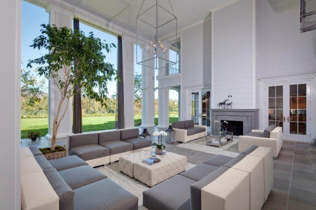 Grey and white living room picture windows glass chandelier grey fireplace slate tile floor modern sofa tufted cube ottoman