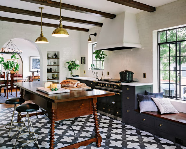 Modern kitchen with a counter height antique wood table with turned legs acting as an island, cement tile floor, and brass pendant lights