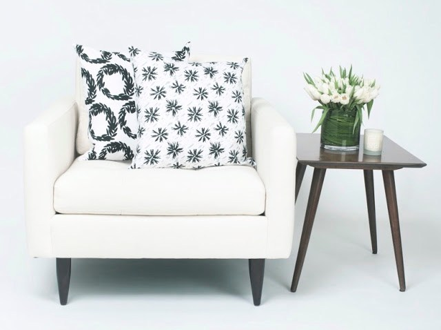 COCOCOZY Light pillows in Rive and Etoile in black and white with a wooden accent table holding tulips and a white candle
