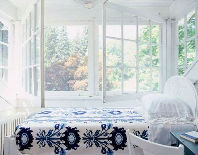 White bedroom with large rustic windows, a wood headboard and blue and white floral bedding