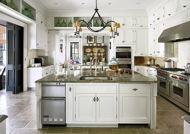 Large Kitchen in a South Carolina estate with stainless appliances, white cabinets and drawers and a metal chandelier