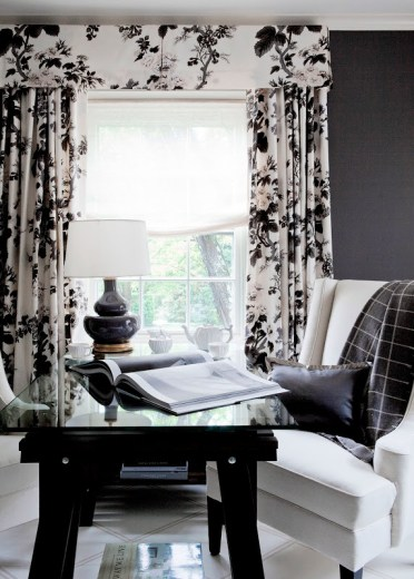 Bedroom with a black writing desk, white armchair with a grey throw, gray walls and chintz curtains