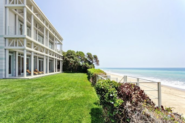 exterior view of a malibu beach front property with lawn and stairs leading directly to the beach