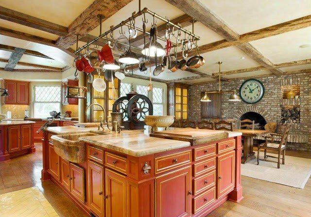 rustic, eat in kitchen in a mansion with red island, cabinets, stone fireplace, antique coffee grinder, hanging pot racks and visible beams