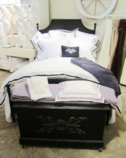 Elegant dark wood bed frame with white bedding with black trim from Downtown Company