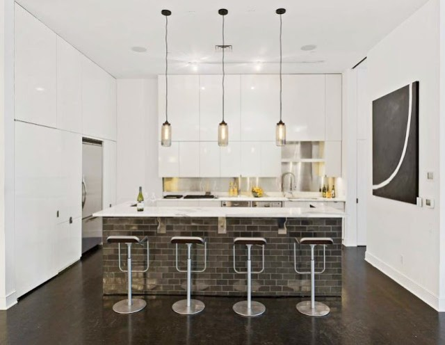 modern kitchen in a Soho Condo in New York with white walls, pendant lights and a brick island