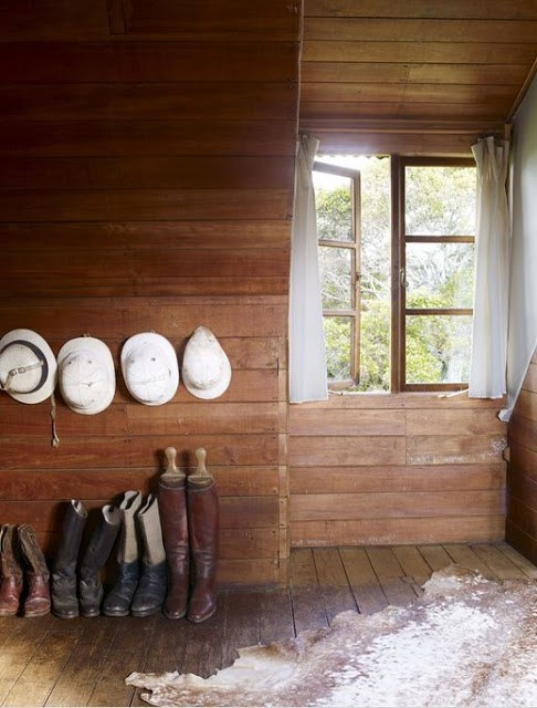 row of boots in a mudrom below kenyan riding helmets hanging on wood plank walls with an animal skin rug