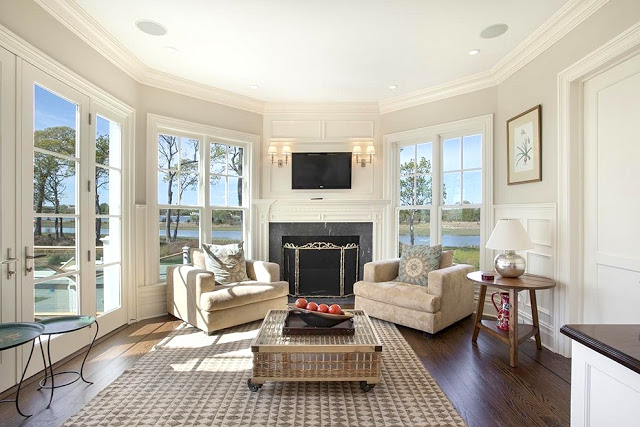 Sunroom bay windows wood floor fireplace Sag Harbor home