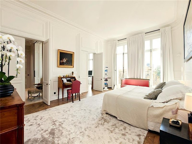 bedroom with paneled walls, french doors, tall windows, a writing desk and high ceilings