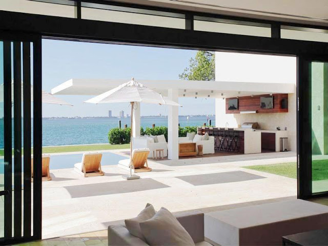 pool view of a Miami mansion with bar, white sofas under an arch and reclining chairs