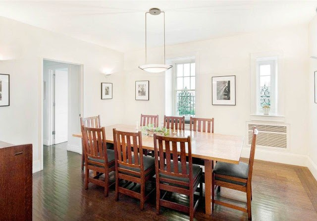 dining room with long wood table, wooden chairs, a pendant light, white walls and framed pictures