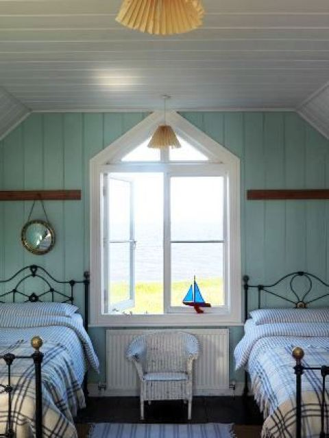 old fashioned iron twin beds with plaid bedding in a preppy beachy guest room with wood floor, a striped rug and a white wicker chair and a large pentagon shaped window overlooking an ocean or lake