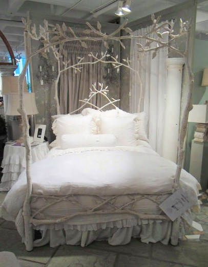 An iron bed frame made to look like tree branches. The bedding is white and very romantic from Pom Pom at Home designed by Hilde Leiaghat.