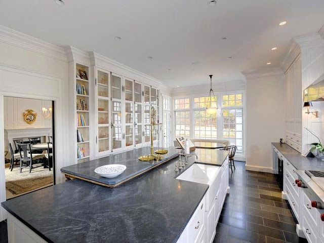 Kitchen with field stone tiles on the floor, white cabinets, dark marble counters, concealed appliances and a glass front book cabinet