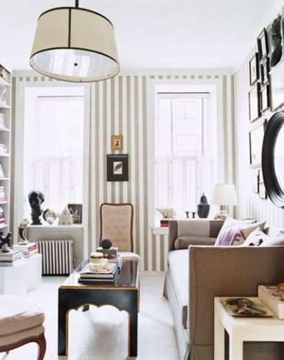 Living room with striped walls, a large white oval pendant light, a taupe sofa, a black accent table and a wall full of different sized picture frames