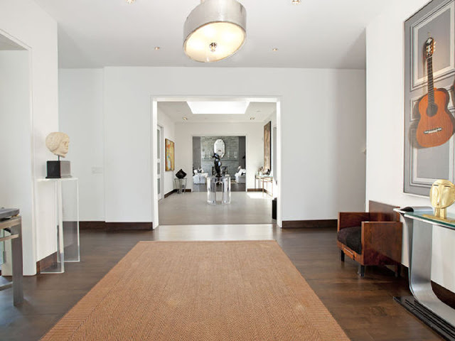 foyer in the Hamptons with wood floors and  woven chevron rug