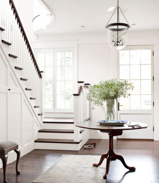 White foyer with wood floor, round table, Persian rug, and glass pendant light