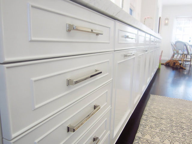 Close up of white panel cabinets with polished nickel drawer pulls