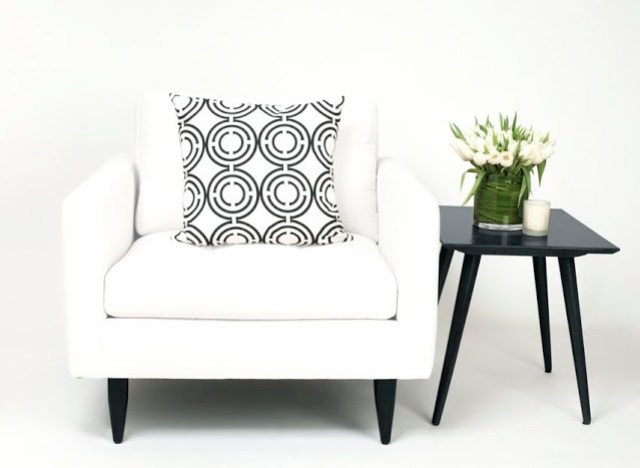 COCOCOZY Light Pillow in black and white on a white armchair with a black accent table, flowers and a candle