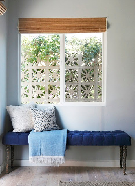 Blue velvet tufted bench with two pillows and a blue throw with white fringe under a window in the corner of a room with hardwood floors