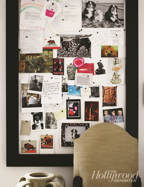 pin board with black frame holding photos and notes on a white wall