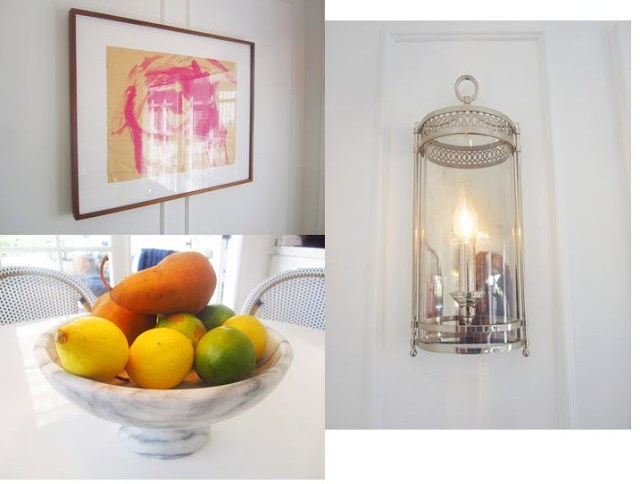 kitchen finishing touches: a polished nickel silver sconce light, marble fruit bowl holding lemons, limes and pears, and a framed piece of a child's art