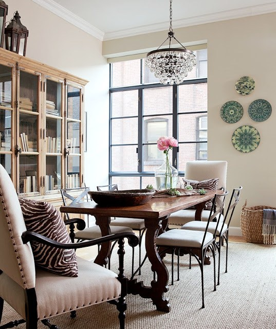 Dining room with floor to ceiling windows with black trim, no curtains, mixed chairs, a traditional wood table, a light build chandelier, wooden cabinet with glass doors and decorate plates on the wall