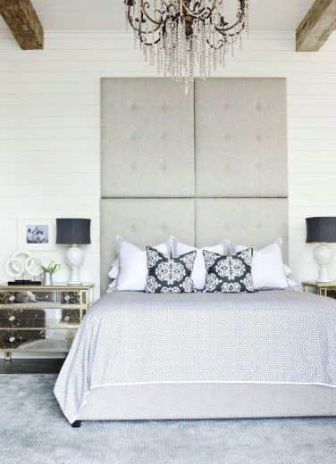 Bedroom with white beadboard walls and exposed beams, high ceiling, a tall, tufted grey headboard, mirrored side table, a grey rug and a crystal chandelier