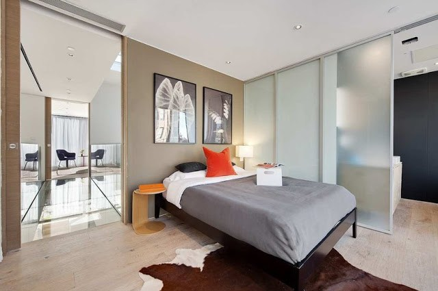 guest bedroom with animal skin rug, sliding door, wooden bed frame and orange accents