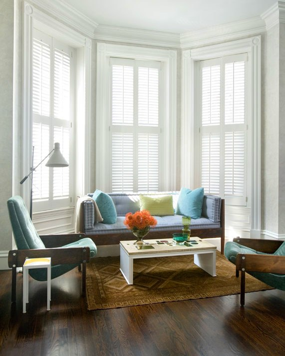 Seating area with tall bay windows with plantation shutters, wood framed settee and armchairs upholstered in shades of light blue