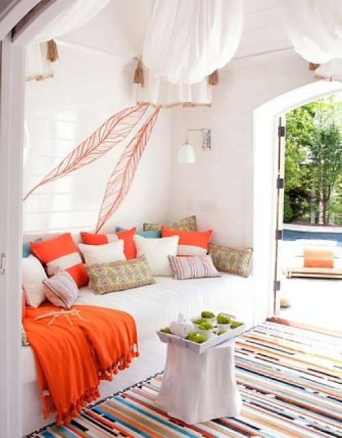Indoor room with white sofa, orange and blue accent pillows, an orange throw and a white table