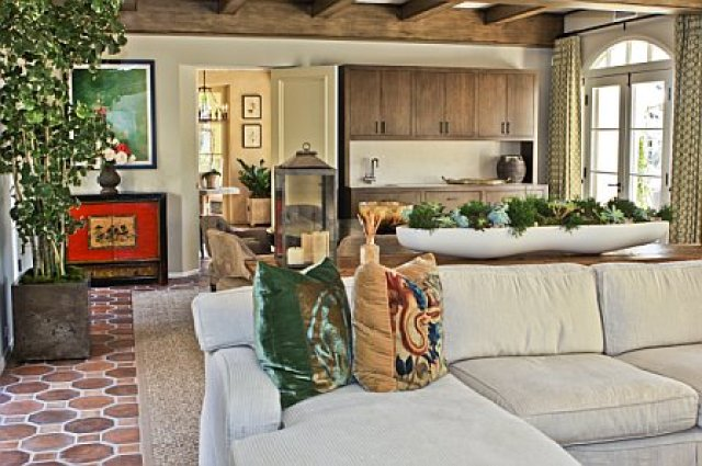 Garage was turned into a media room after remodeling with natural wood beamed ceiling, spanish tile floor, white sofa and a flat screen TV