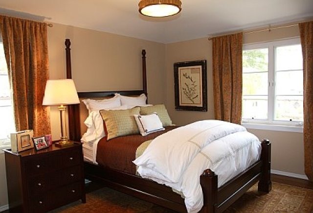 Taupe guest bedroom with a dark wood bed and matching nightstand
