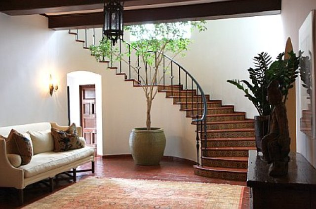 Foyer with a light colored settee and rug after remodeling and repainting