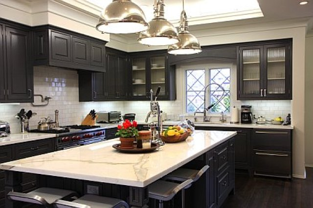 Kitchen after remodeling with Calcutta Gold marble countertops, dark brown painted wood cabinets, new windows, subway tile backsplash and pendant kitchen island lighting