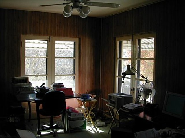 Guest bedroom with wood paneling before remodeling