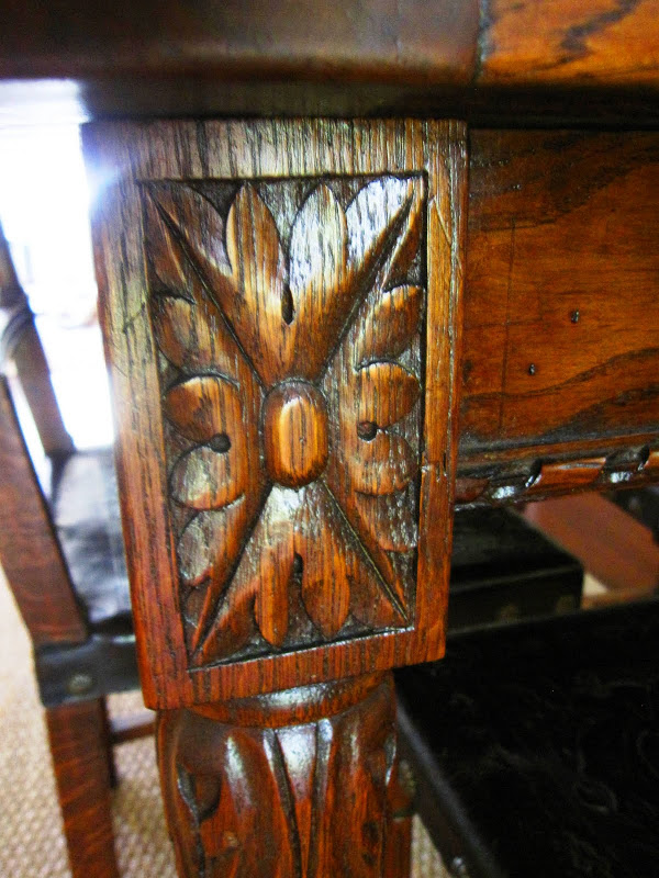 Close up of the carved details on an antique dark stained wood dining table