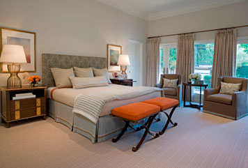Bedroom by Massucco Warner Miller with orange x-benches at the foot of the bed, grey armchairs, curtains and upholstered headboard
