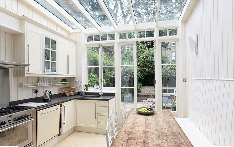 Kitchen in a London home with glass ceiling, white paneled walls, dark stone counters and white cabinets