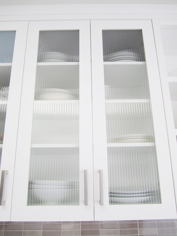 White painted wood cabinets with glass paneled doors
