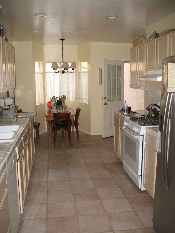 Narrow kitchen with old cabinets and countertops