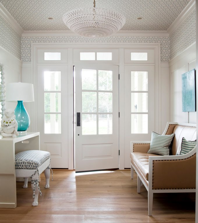 Foyer with light wood floor, graphic painted ceiling, white desk with a white upholstered ottoman, blue glass lamp and a sofa with white and tan sofa with nail head trim