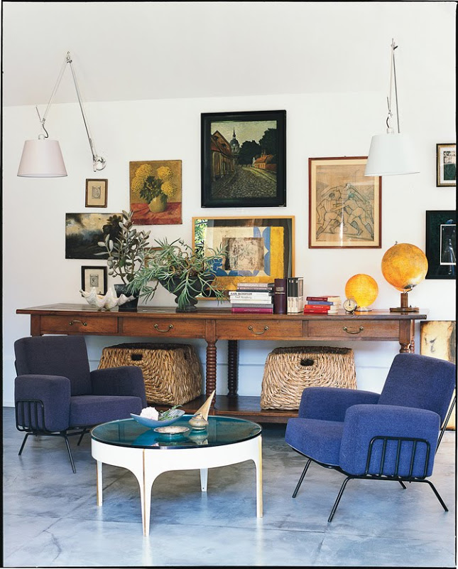 Den with blue tile floor and armchairs, a round coffee table, a long wood table with wicker baskets and two white wall mounted lights