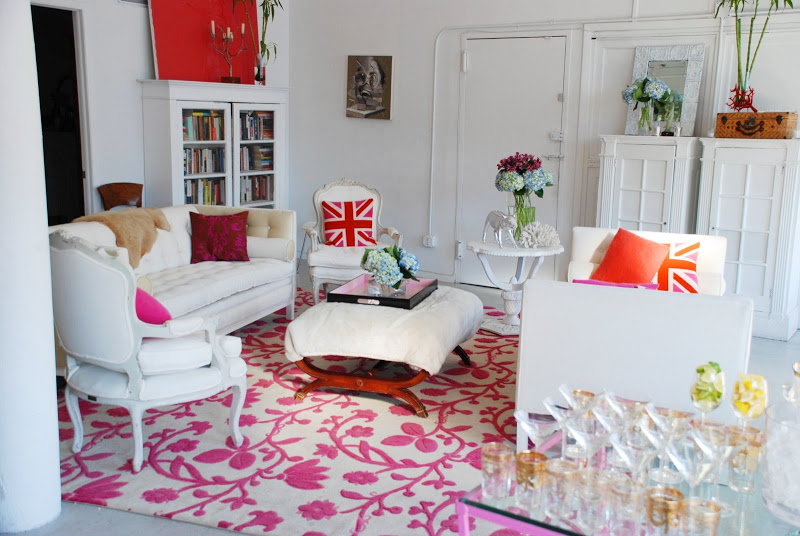 White living room in a NYC loft a tufted sofa, chaise lounge, upholstered Louis XIV chairs, an ottoman with wood legs on a pink and white area rug