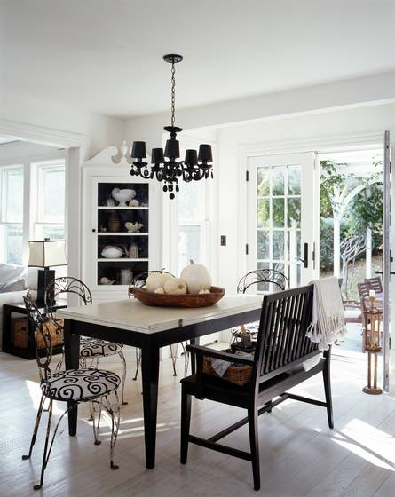 Black and white dining room in a cottage with a light wood floor, table with black legs and a marble top, black chairs with white and black graphic print seats, a dark wood bench, black chandelier, white cabinet and french doors