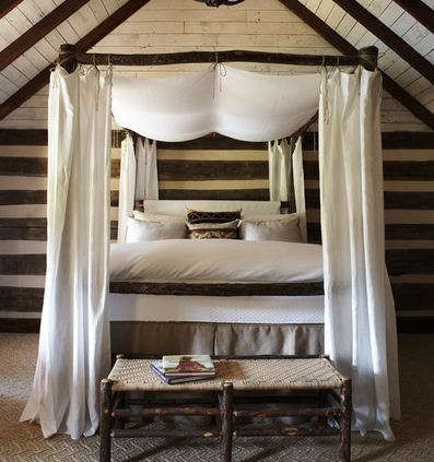 Bedroom with painted black visible beams, black and white striped walls, a canopy bed, a reclaimed wood bench with woven seats is at the foot of the bed and a carpeted floor
