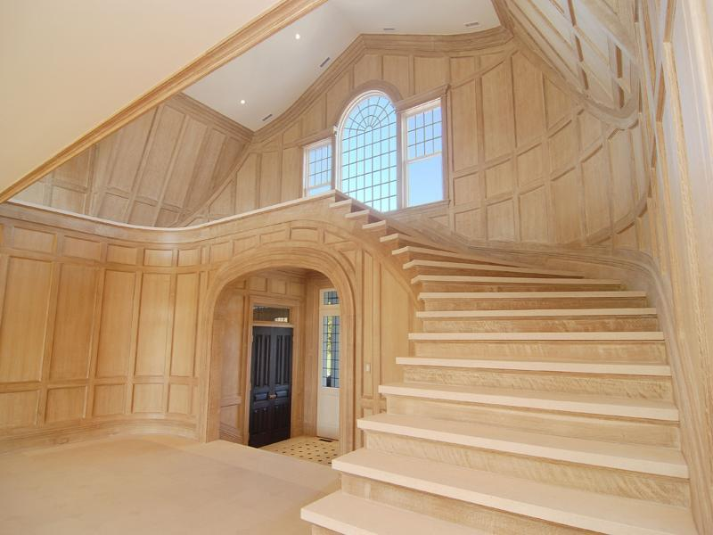 Empty foyer in a Hamptons farm with light wood paneling, high ceiling and a staircase with no railing