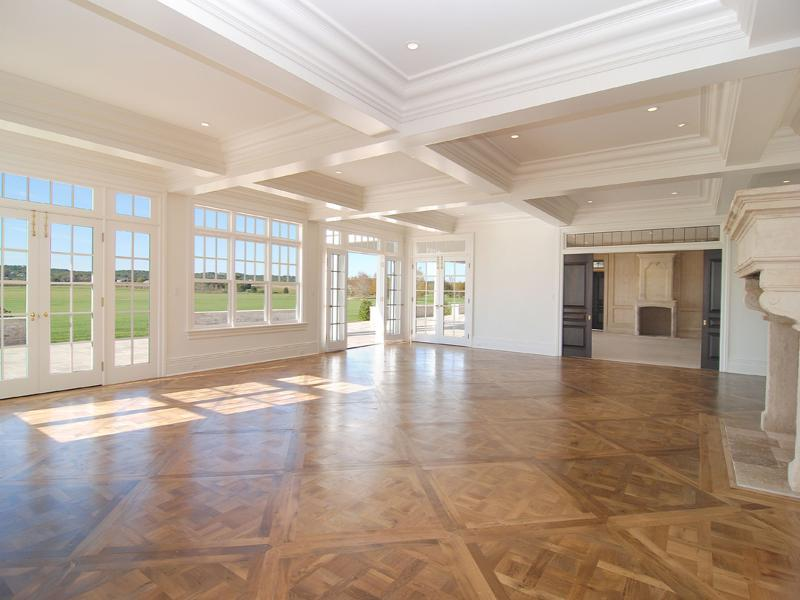 Empty living room in a Hamptons farm with coffered ceiling, large windows, wood floor and a massive fireplace